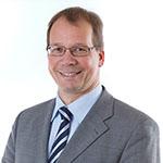 Mann mit Brille, Schlips und grauer Anzugjacke lächelt in die Kamera