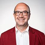 Mann mit Brille und roter Anzugjacke lächelt in die Kamera