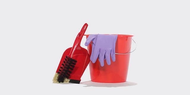 eine rote Kehrschaufel und ein Besen, daneben steht ein roter Eimer, darauf liegen Gummihandschuhe