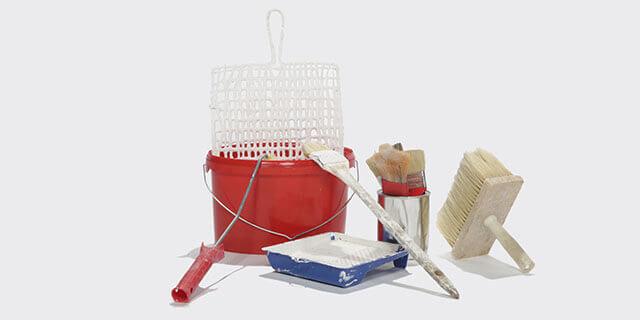Malerwerkzeug: ein roter Eimer mit einem Rollersieb, ein Handroller und diverse Pinsel