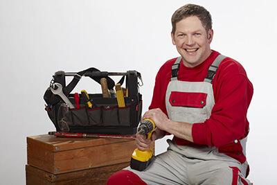 ein Mann im roten Pullover und grauer Latzhose sitzt neben einem Werkzeugkoffer, er hat einen Akkuschrauber in der Hand