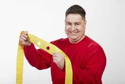 ein junger Mann hält eine gelbe Maske vor sich. Es ist die gleiche Person, die als Superman für den Hauswirtschaftsservice steht.