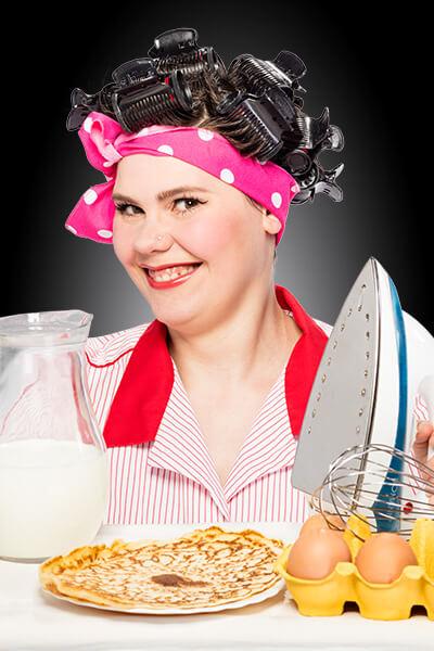 junge Frau lächelt in Kamera, hat Lockenwickler im Haar und hält ein Bügeleisen und Eierkuchen vor sich