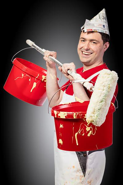 ein Mann in weißer Latzhose stemmt einen Maler-Roller, an dem zwei rote Malereimer hängen