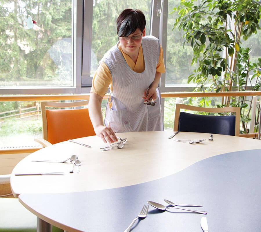 Junge Frau deckt Tisch