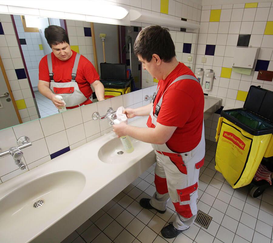 Junger Mann mit Spiegelbild putzt ein Waschbecken