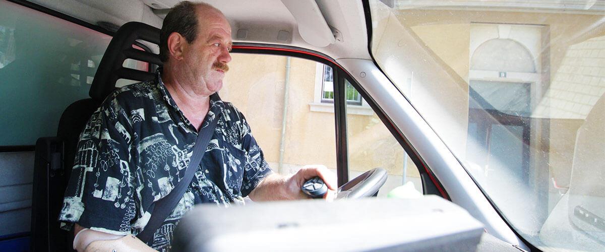 Mann mit Hakenhand am rechten Unterarm am Lenkrad seines LKW