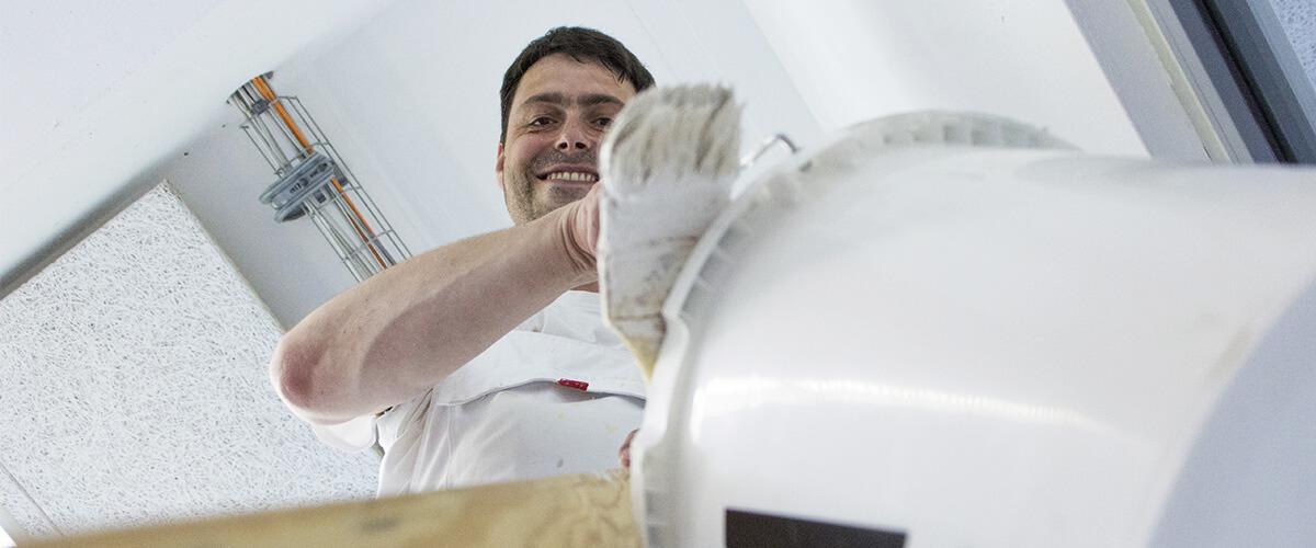 Ein junger Maler steht auf einer Leiter an der ein Farbeimer mit Pinsel hängt. Er schaut nach unten und lächelt in die Kamera.
