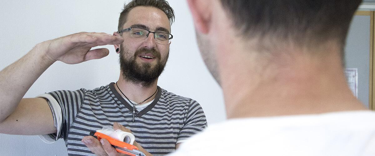 Ein junger Mann mit Bart und Brille erklärt mit seinen Händen, dass etwas groß ist. Ein anderer junger Mann steht vor ihm und schaut ihn an.