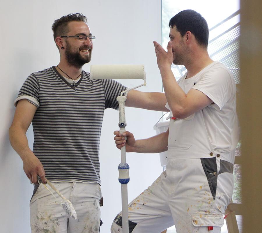 zwei junge Maler schauen lachen miteinander, der rechte hält einen Roller in der Hand