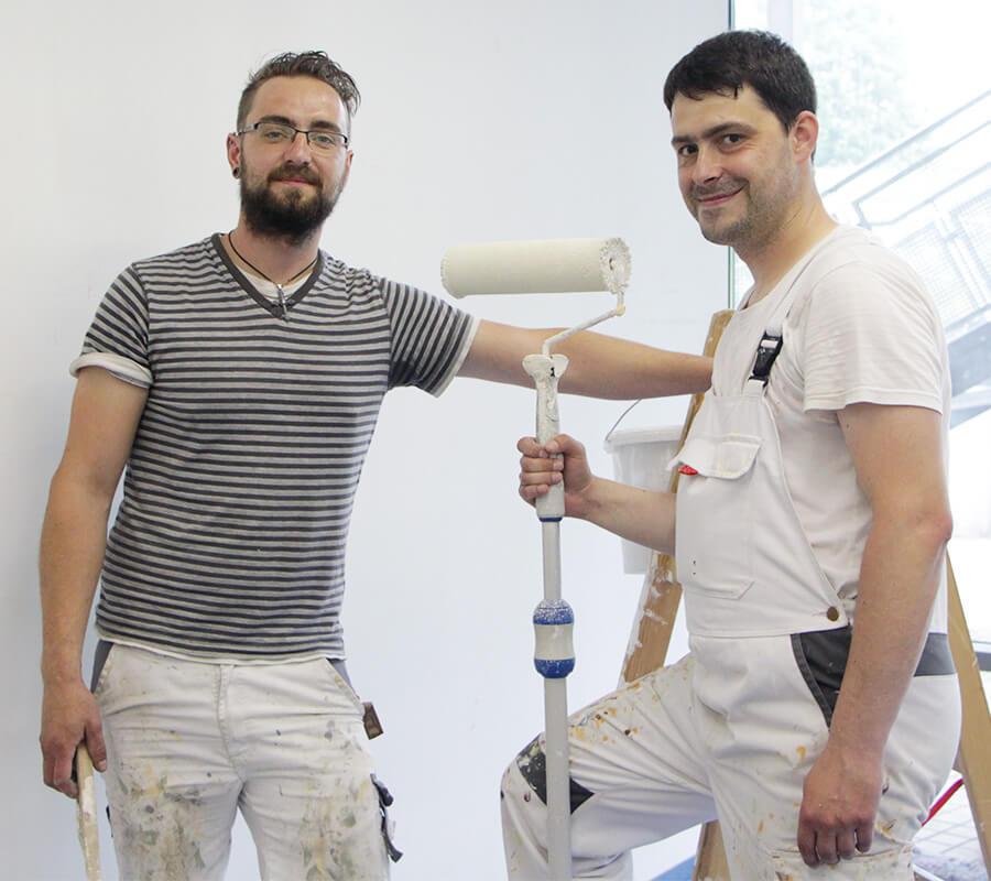 zwei junge Maler schauen in die Kamera, der rechte hält einen Roller in der Hand