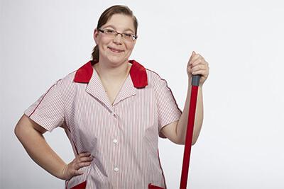 eine junge Frau im Kittel stützt sich auf einem Wischmopp ab
