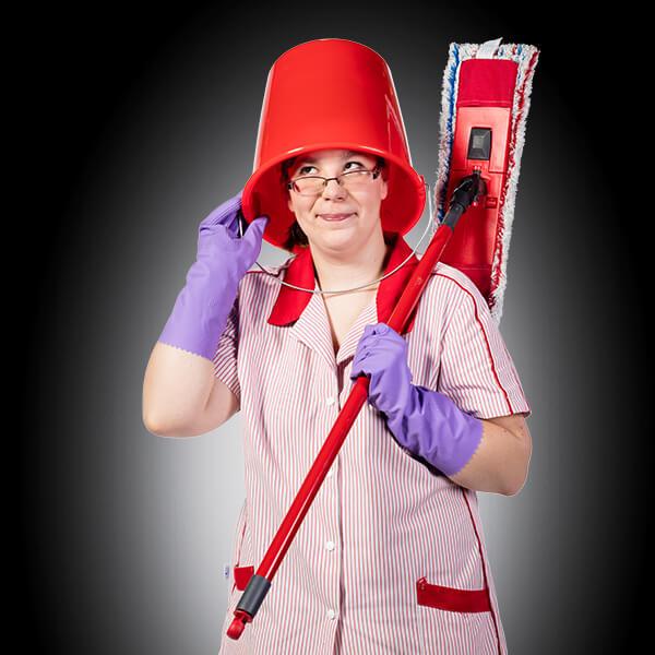 eine Frau in Kittel und Gummihandschuhen hat einen roten Eimer auf dem Kopf, unter dem sie vorsichtig hervorschaut. Über der Schulter trägt sie einen Wischmopp.