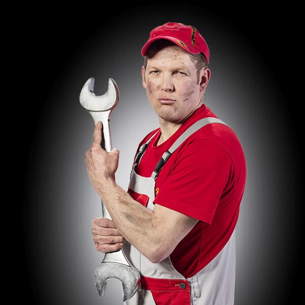ein Mann schaut fordernd in die Kamera, er hält einen überdimensionierten Maulschlüssel in der Hand