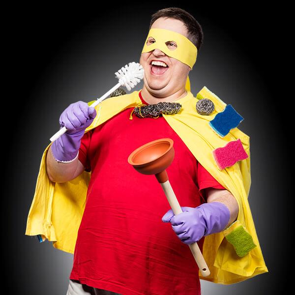 ein Mann mit gelber Maske und gelbem Umhang hält eine Klobürste und einen Pömpel in der Hand. Er sieht aus wie ein Superheld.