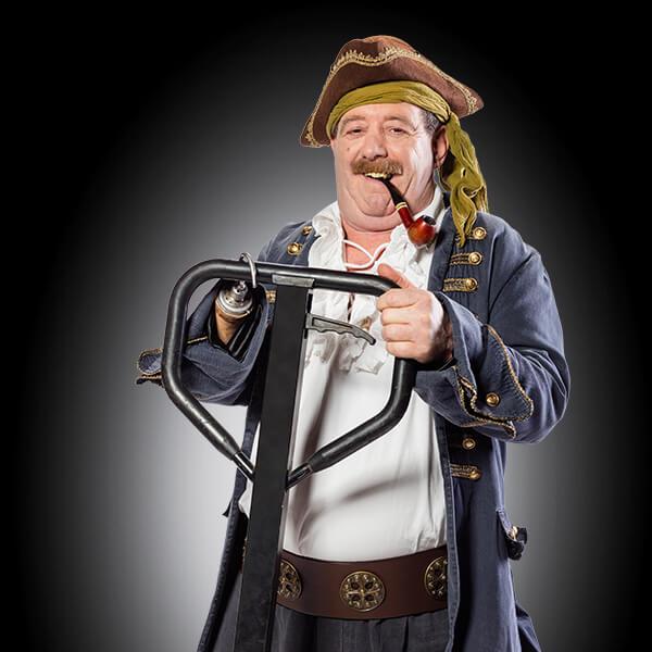 ein Mann im Piraten-Outfit, er steht auf einem Hubwagen, sein linker Unterarm besteht aus einer Hakenprotese