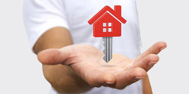 Hand mit rotem Schlüssel in Hausform